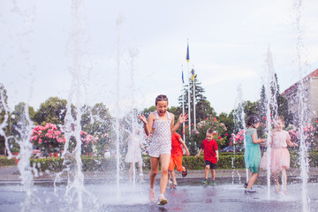 Happy children are playing in a fountain
