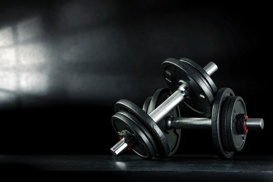 Dark interior of gym with shadow of window and dumbbells on desk.