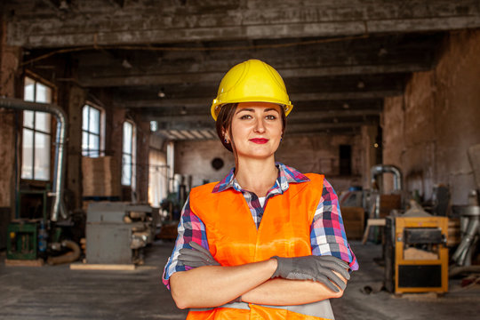 Portrait of woman in hard hat and protective gloves