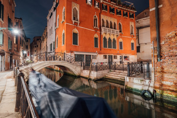 Venice Gondola boat in small channel with arch bridge in lagoon city Venice at night. long exposure Venezia Italy