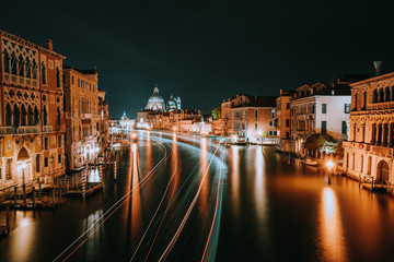 Venice night scenery. Light illuminated trails of ferries and boats reflected on the Grand Canal surface. Majestic Basilica di Santa Maria della Salute in background. Italy
