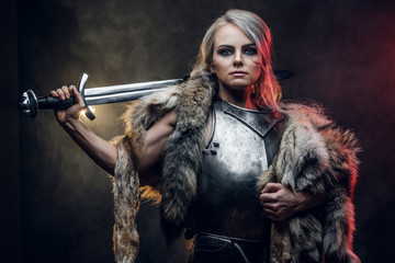 Portrait of a beautiful warrior woman holding a sword wearing steel cuirass and fur. Fantasy fashion. Studio photography on a dark background. Cosplayer as Ciri from The Witcher.