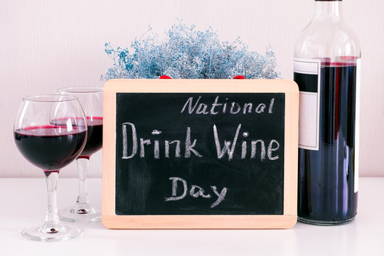 Blackboard with words National Drink Wine Day on the table with wine bottle and two glasses with wine.