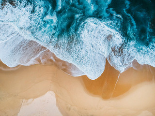 Blue ocean waves aerial drone shot on sandy beach