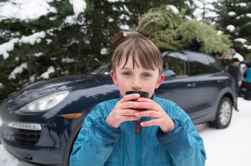 A boy drinks hot chocolate after getting a Christmas tree.