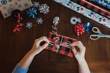 Hands wrapping present and gift wrapping supplies on wooden table.
