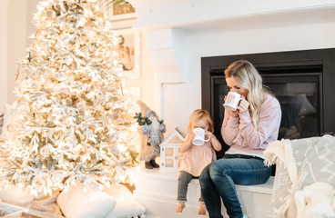 Mother and baby drinking from mugs by christmas tree