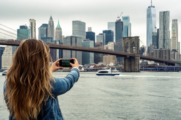 attractive woman using her smartphone with the New York skyline in the background