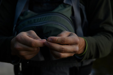 A man's hands tying on a small fly for fishing.