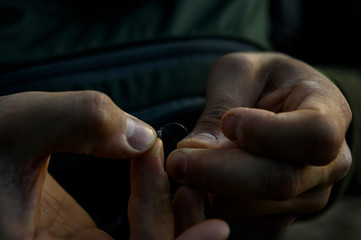 A fly fisherman ties on a tiny fly to tippet.