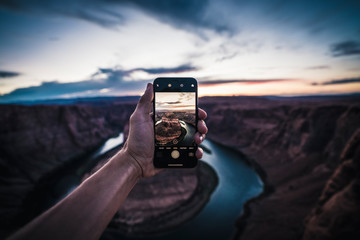 Young Man holding iPhone, photographing sunset at Horseshoe Bend