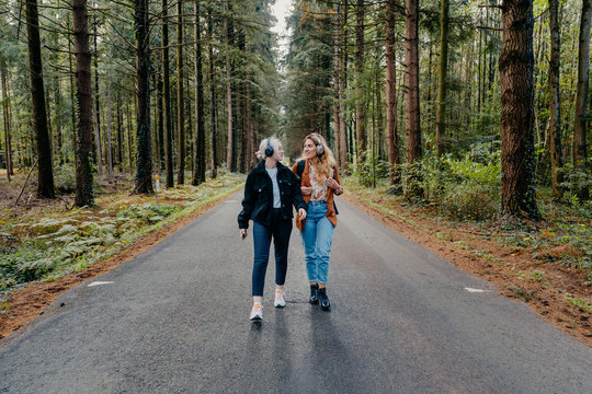 Two women walking on a road in the forest while listening to music
