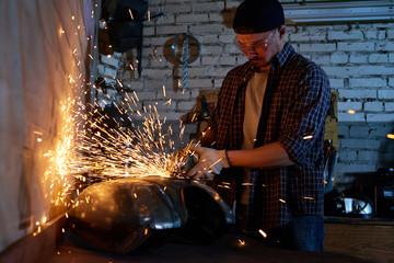 Young repairman grinding motorbike fuel tank part in his workshop