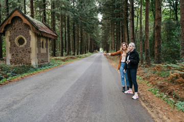 Two women hitchhiking on a forest road in France
