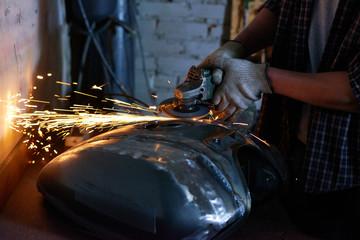 Repairman wearing checked shirt grinding motorbike fuel tank part