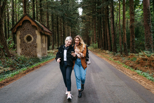 Two women walking down the road looking at their phone and laughing