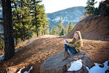 Young Redhead Girl Sitting on a Rock in the Sunshine on Mountain Path