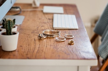 Woman's silver jewellery on a desk next to a computer Wall mural
