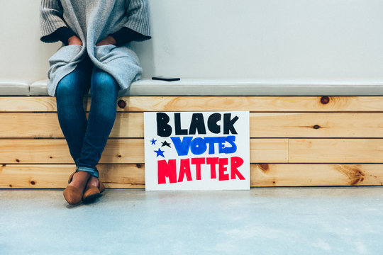 Person sitting with their Black Votes Mstter sign