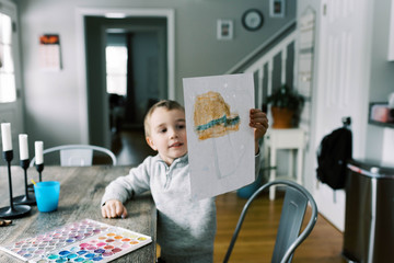 Little boy spending an afternoon painting with watercolors.