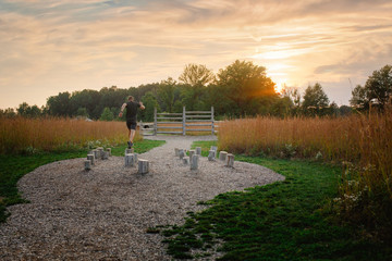 A man runs across series of wooden beams in obstacle course at sunset