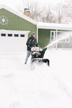 Man snowplowing his driveway during a winter storm.