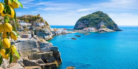 Rocky coast of Sant'Angelo, giant green rock in blue sea near Ischia Island, Italy. Sant'Angelo is small village within comune of Serrara Fontana, Ischia.