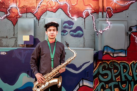 High school jazz band musician posing with saxophone by graffiti