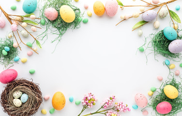 Top down view of an Easter border frame of robin's eggs and chocolate eggs with copy space in the middle