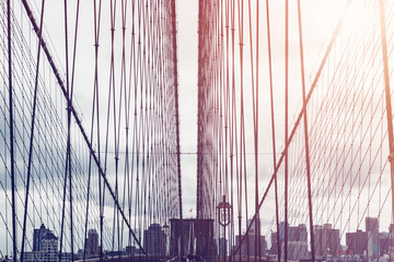 Details of the Brooklyn Bridge in New York City, USA. Toned image with sun light leak