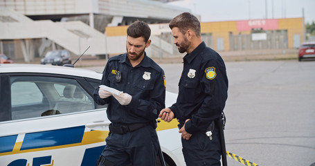 Two policemen find drugs collect evidence for crime investigation. Police officers colleagues discussing a crime scene standing near the police car outdoors.