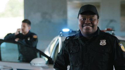Happy african american young man cops stand near patrol car look at camera smile enforcement officer police uniform auto safety security communication control policeman portrait close up slow motion