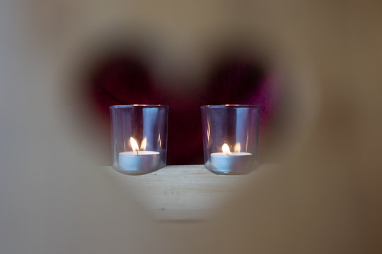 Valentine's day, blurred heart of a peephole in wooden chair with candle glass in focused background.