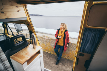 Young blond woman standing next to camper van overlooking the sea