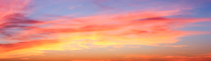 Foto op Canvas Ochtendgloren Beautiful red and orange cloud formations at sunrise in a panorama sky view
