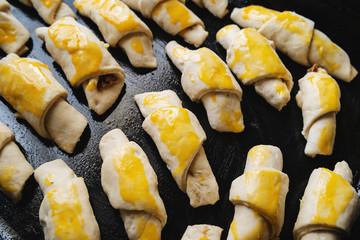 Raw serbian kifla cheese crescent rolls egg glazed homemade ready to bake high angle view on black casserole dish