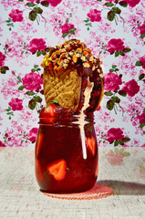 Cookie with nuts in jar of strawberry marmalade