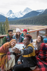 Happy friends taking selfie with camera phone on cabin balcony with mountain view, Rocky Mountains, Canada