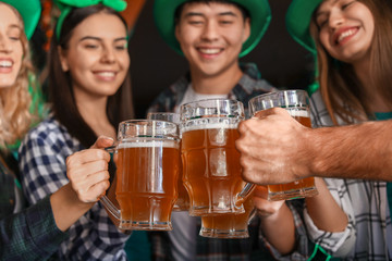 Young friends with beer celebrating St. Patrick's Day in pub