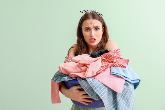 Funny housewife with laundry on color background