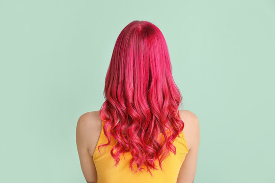Beautiful young woman with unusual hair on color background
