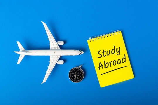 STUDY ABROAD - message on blue background with airplane model. Learning a language and studying abroad