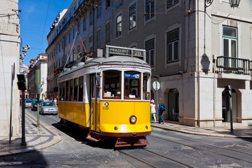 LISBON, PORTUGAL - JUNE 22, 2013: Yellow tram of the Route #28 on the street of Lisbon. It is one of the most popular routes by tourists. Lisbon tramway network operates since 1873