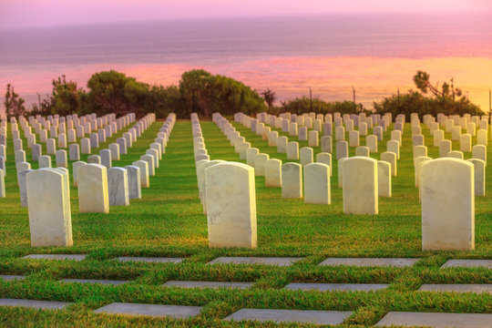 Cemetery graveyard white tombstones at colorful sunset sky. American war cemetery in Point Loma, San Diego, California, United States with rows of gravestones towards the ocean.