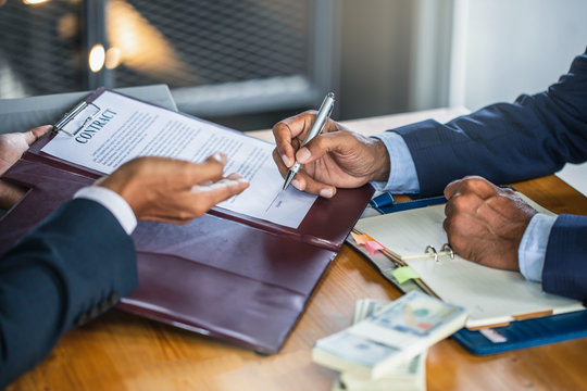 Customer shaking hands after signing contract documents for realty purchase, Bank employees congratulate, Concept mortgage loan approval. Business loan from a bank employee. finance concept .