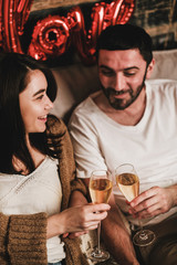 Young smiling happy couple in love in comfortable home clothing clinking glasses of champagne and celebrating holiday at home. Valentines day celebration concept
