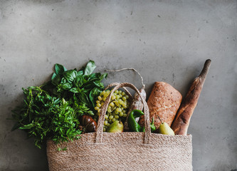 Flat-lay of healthy grocery shopping eco-friendly bag with fresh vegetables, fruit, greens, herbs, bread and sausage over concrete background, top view, copy space. Local farmers market concept
