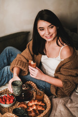 Young beautiful smiling brunette woman in comfortable home clothing having breakfast in bed with tea, croissants, jam and strawberries at home. Comfortable lifestyle concept