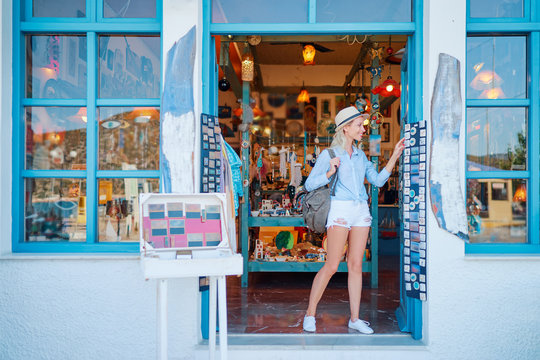 Travel and shopping. Young traveling woman with backpacks choose postcards in souvenir shop in Greece.