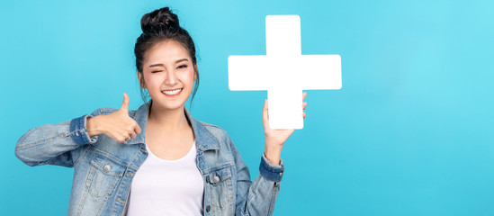 Banner of asian woman smiling, showing plus or add sign and thumb up on blue background. Cute asia girl wearing casual jeans shirt and showing join sign for increse and more benefit concept